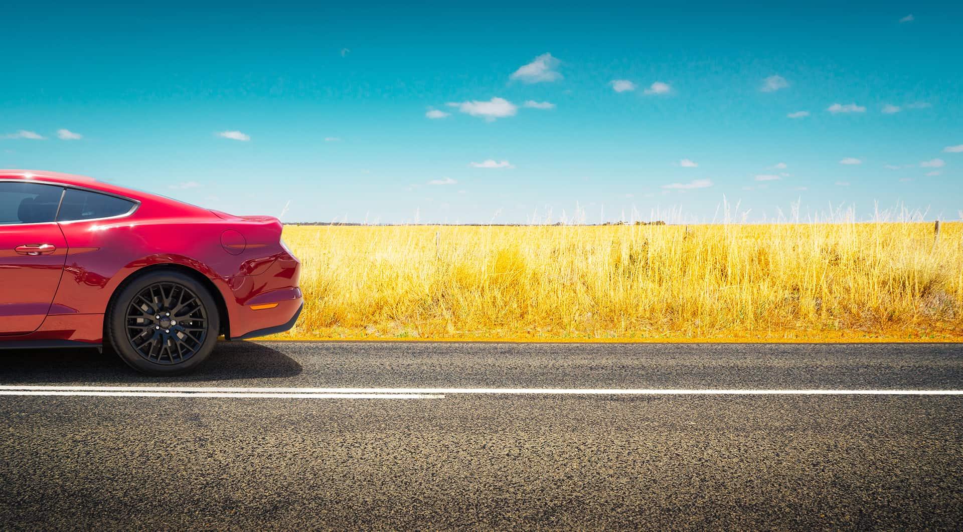 auto rossa parcheggiata accanto ad un prato